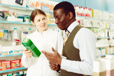 young woman pharmacist explaining prescribed medicine to her customer